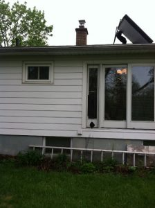 Haslett Rear Addition Before - Built new addition on rear of house.  Vinyl siding, vinyl sliding windows, custom eyebrow windows.  New exterior door.  Built new landing and steps with Azek decking.  New storage shed at end of driveway.