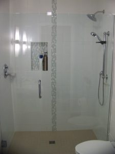 Lansing Aging in Place Bathroom Remodel - Description: Tile shower with low threshold, glass enclosure, handheld shower head on grab bar.