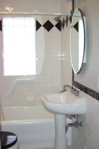 Lansing Bathroom Description: Tile wainscoting, tile tub surround, tile floor, new toilet, glass block window, new pedestal sink.