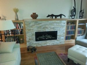 East Lansing Gas Fireplace Description: Installed new gas fireplace.  Installed stone ledgers. Installed bookcase around.  Furnished custom mantel.